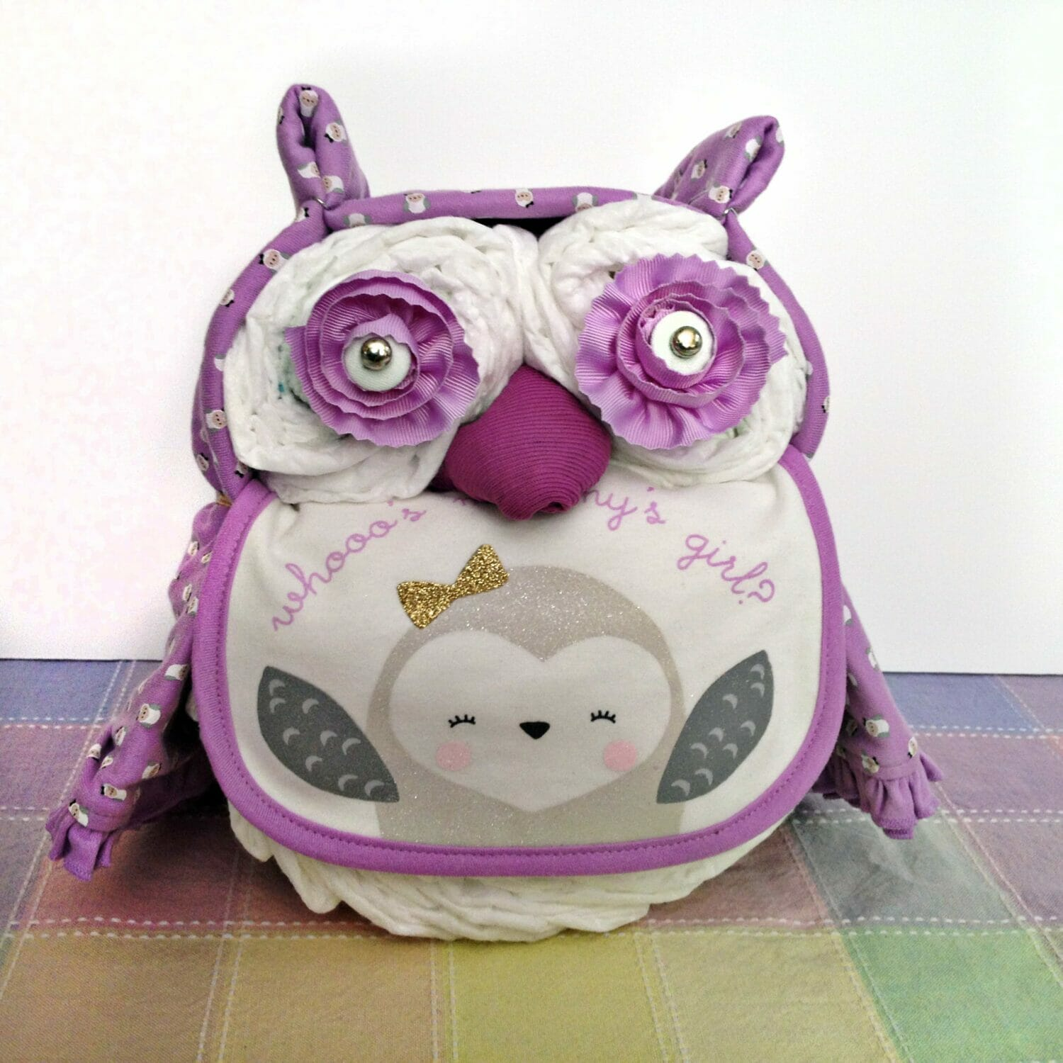Owl themed diaper cake made with a purple baby blanket, purple bib and flower eyes sitting on a pastel tablecloth.