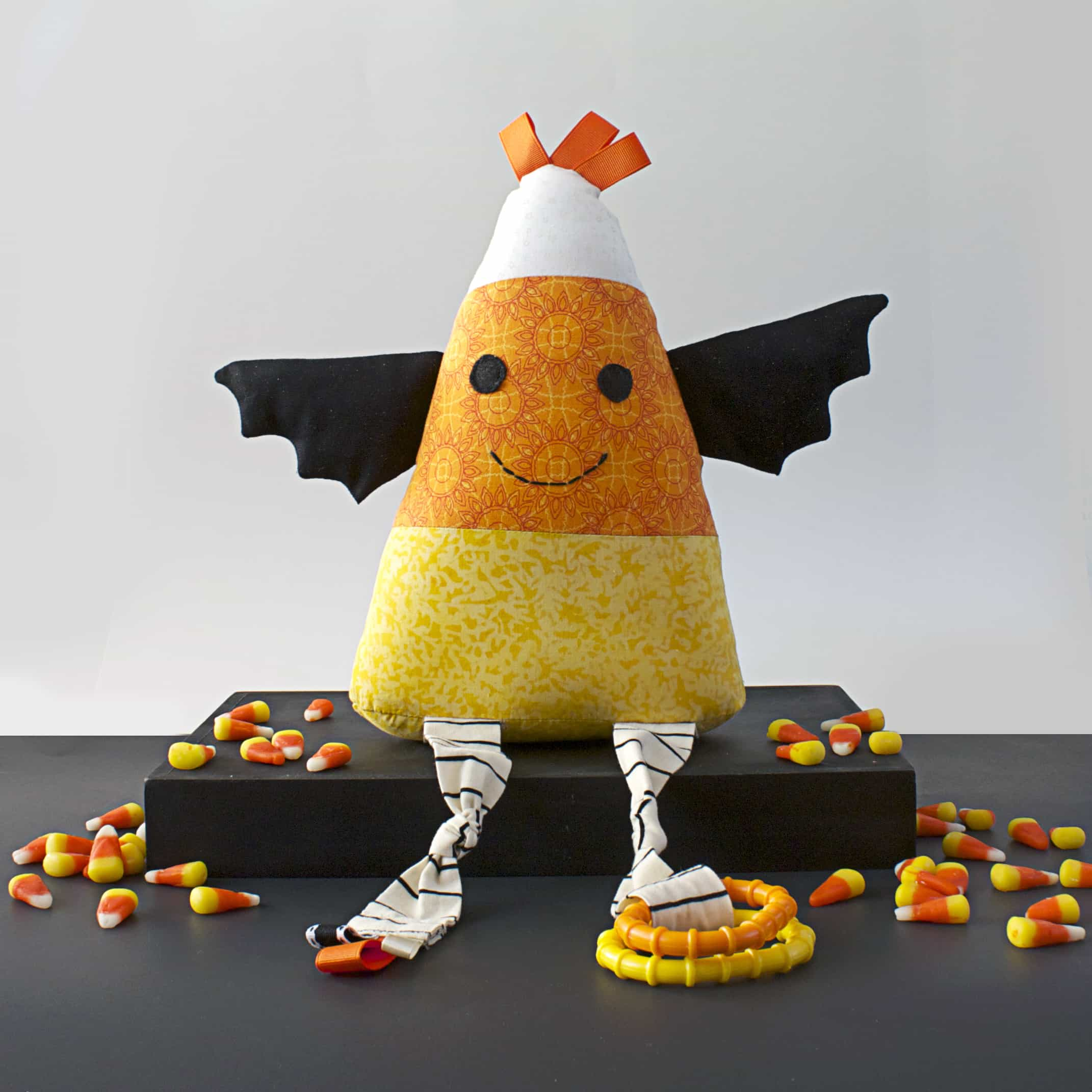 Cute candy corn stuffed toy sitting on a black tabletop with candy corn around it.