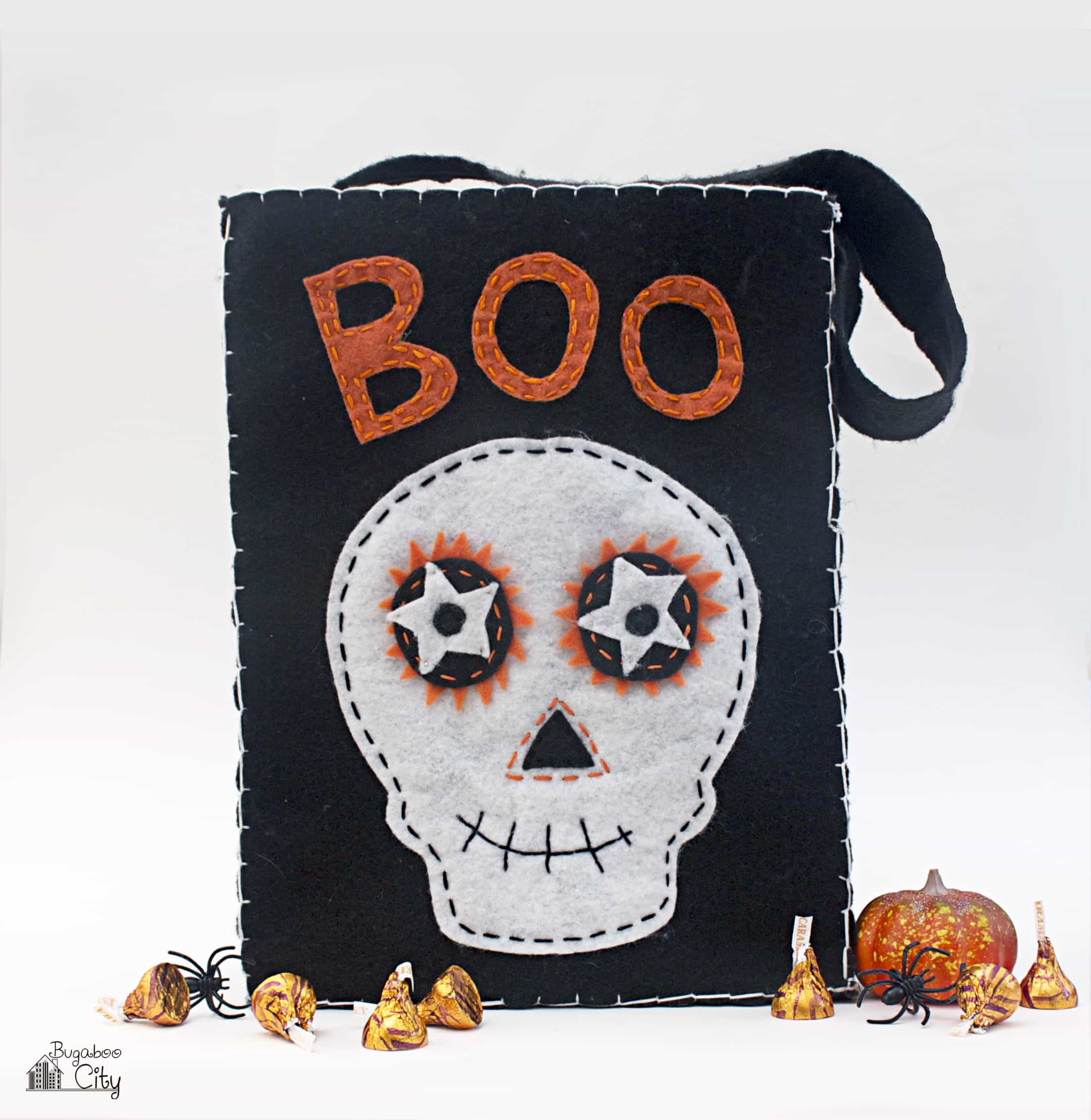 "Black felt Halloween treat bag with a skeleton face and the word ""BOO""."