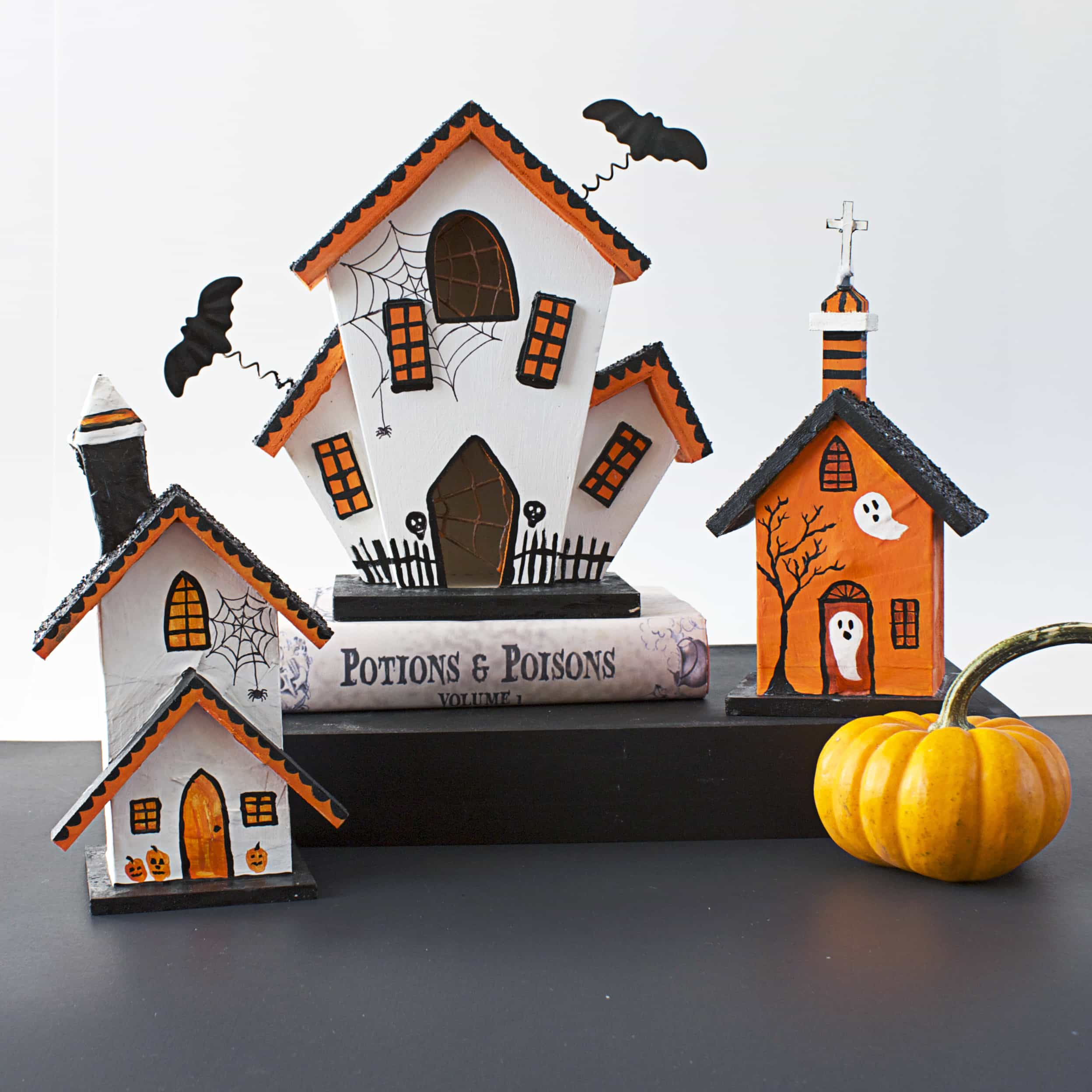 Three wooden birdhouses painted in white, black and orange sitting on a black table with a small orange pumpkin nearby.