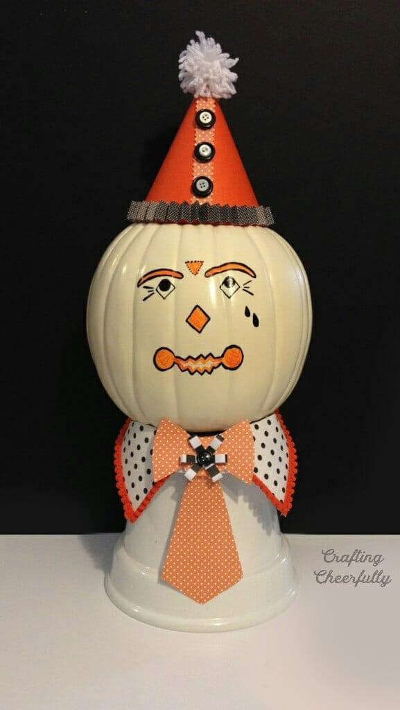Vintage clown pumpkin sitting on an upside down pot.