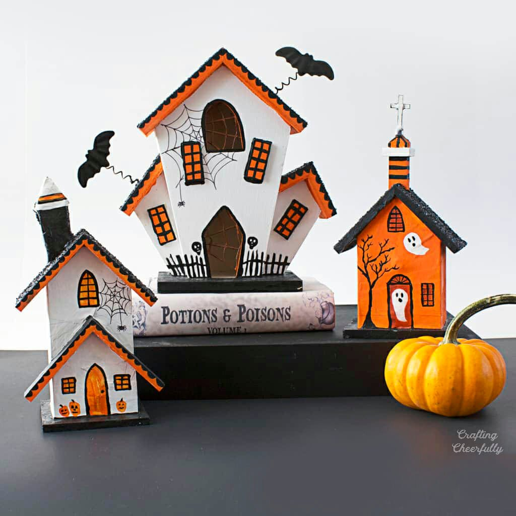 Three haunted houses made from unpainted birdhouses sit together on a black table.