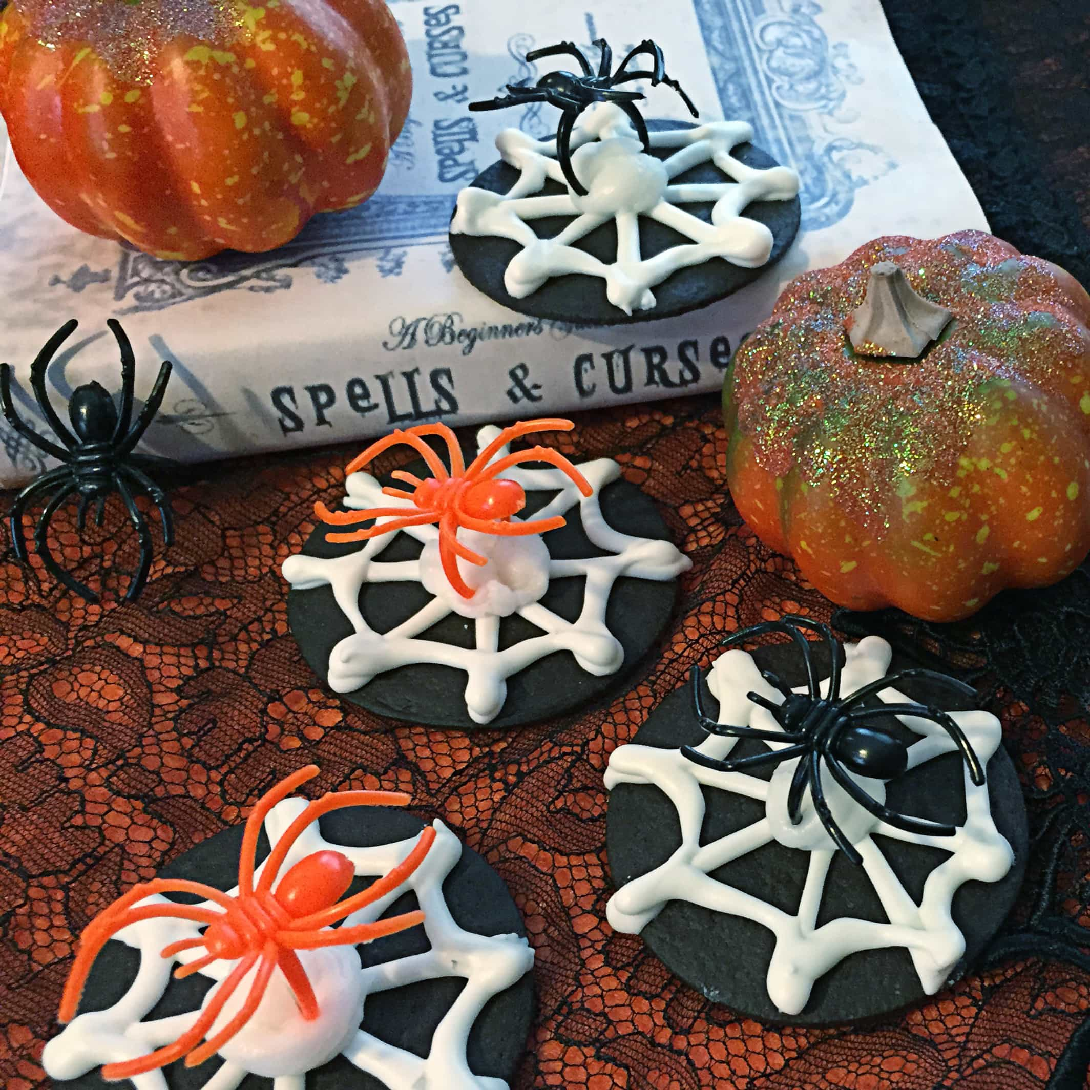 Halloween cookies that look like spider webs with plastic spider rings on them sit on a tabletop decorated for Halloweenl.