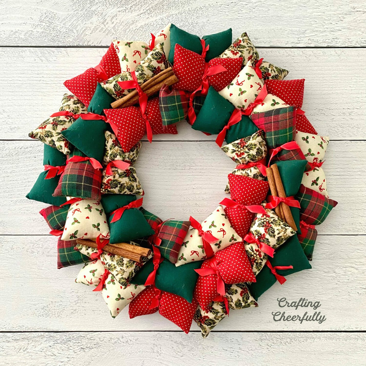 DIY holiday pillow wreath using Christmas fabrics in red, green and white lays on a white wooden table.