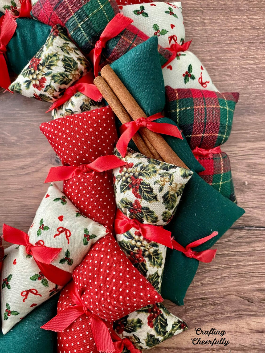 DIY holiday pillow wreath using Christmas fabrics in red, green and white lays on a wooden table.