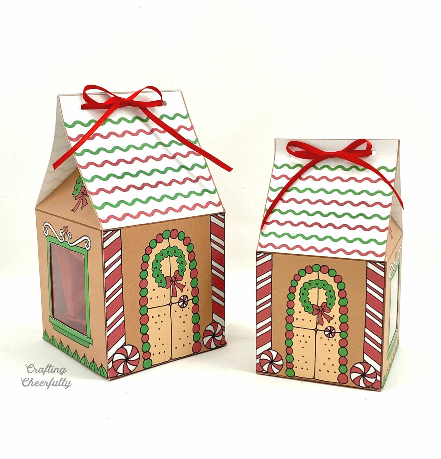 Two gingerbread house treat boxes sit next to each other.