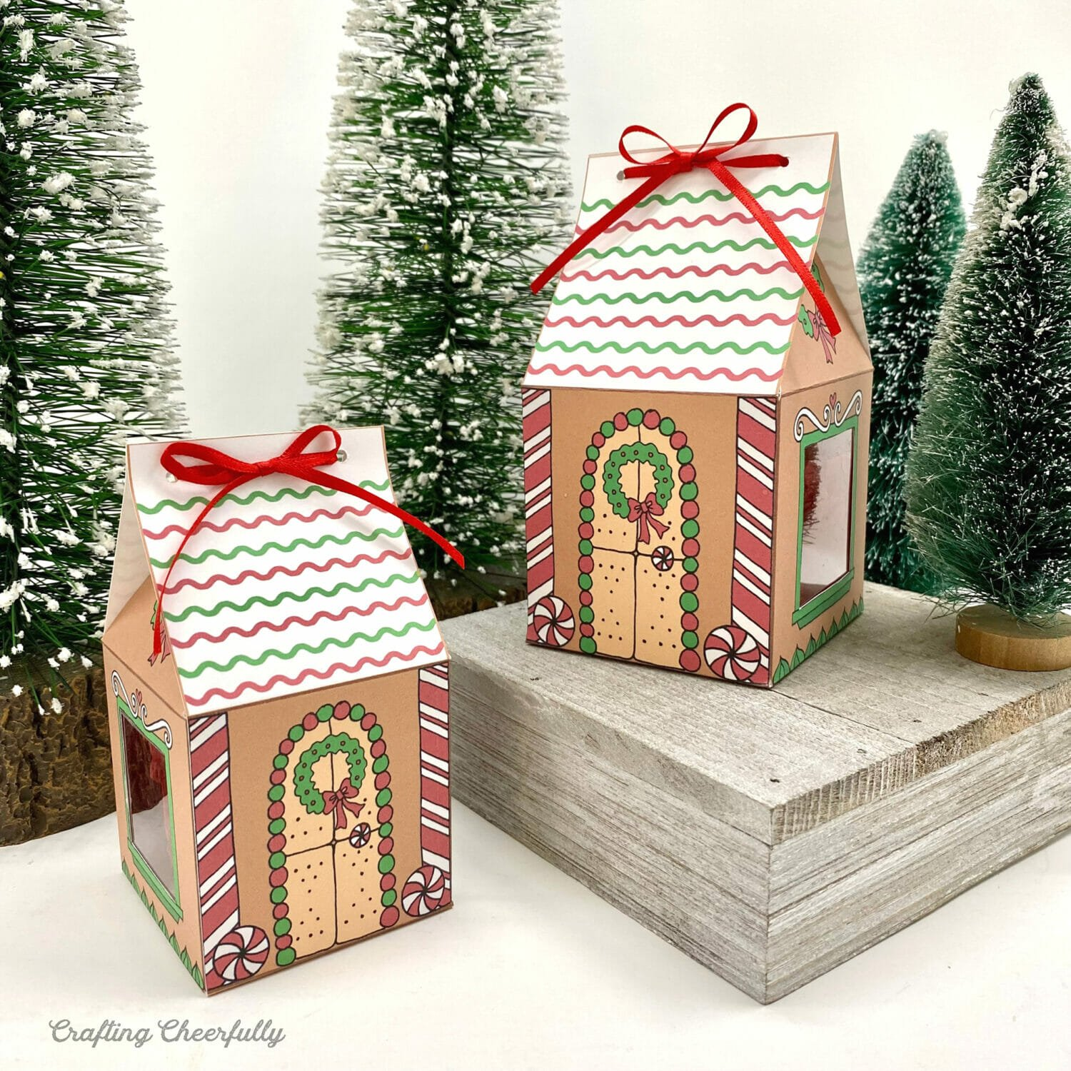 Printable Christmas gingerbread house boxes sit next to Christmas trees.