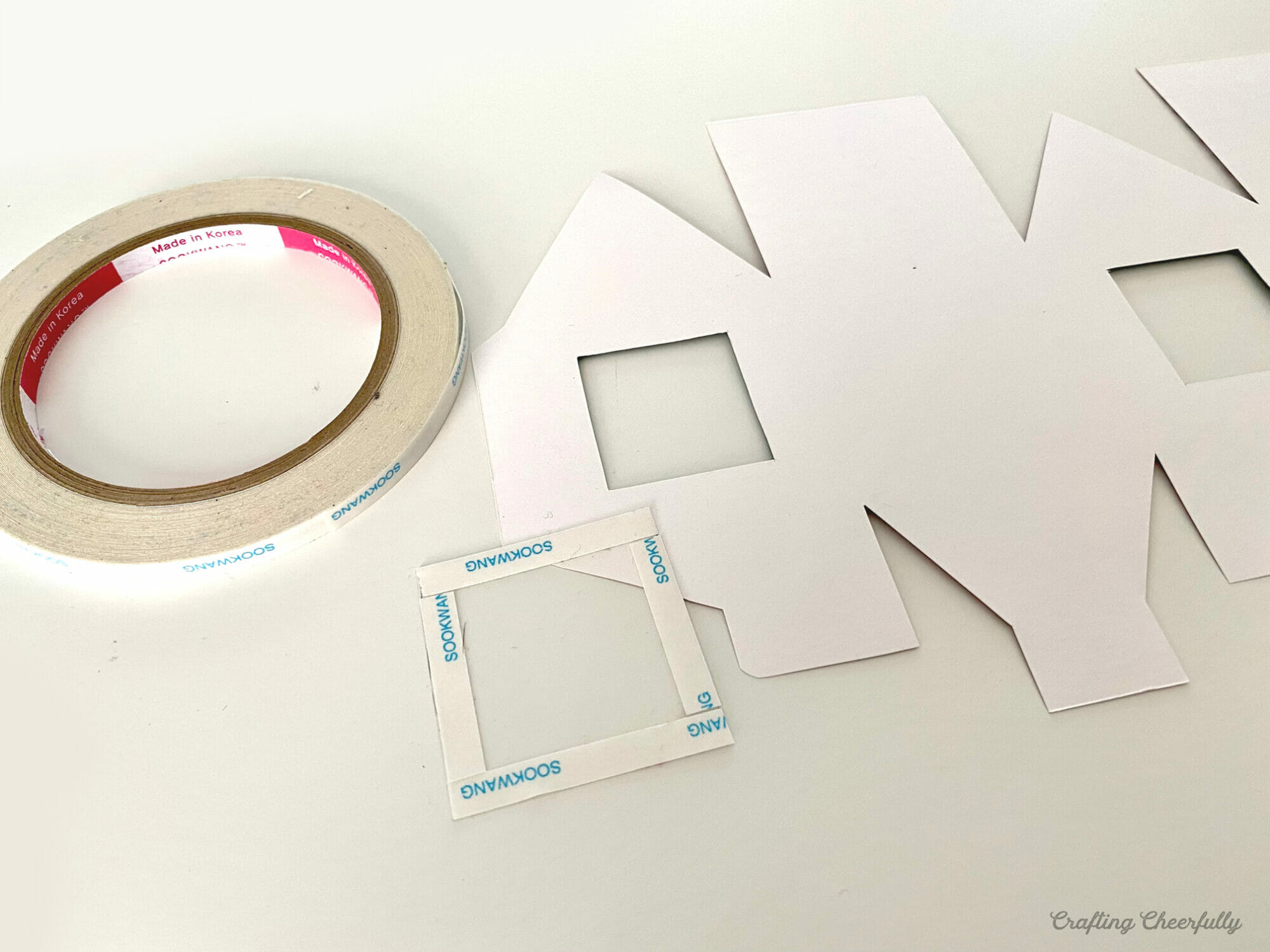 A printable gingerbread box lays on a table with clear craft plastic.