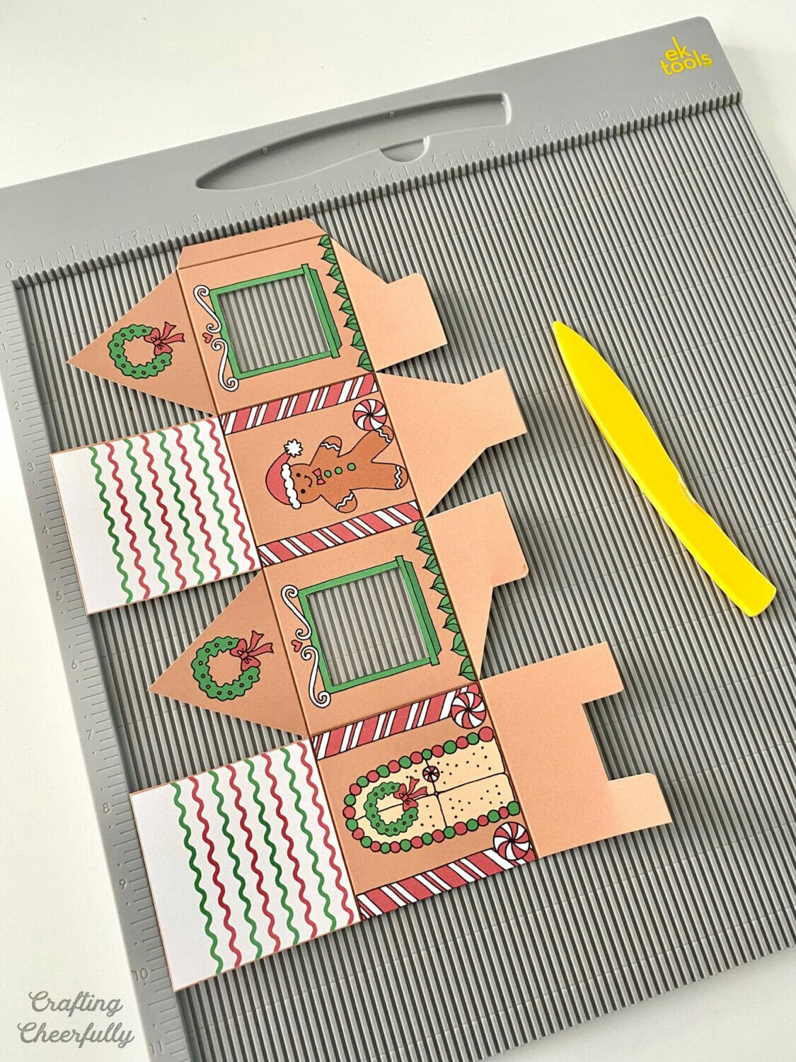 A printable gingerbread treat box is on a scoring board next to a yellow scoring stylus.