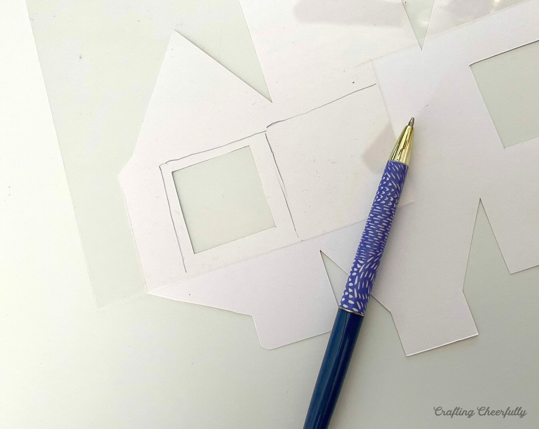A printable treat box lays upside down next to a piece of craft plastic and a pen.