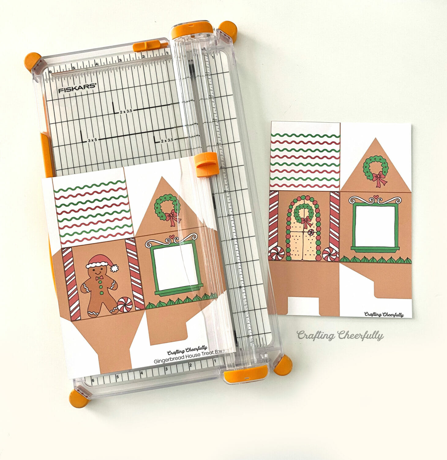 A printable gingerbread house treat boxes getting trimmed with a paper trimmer.