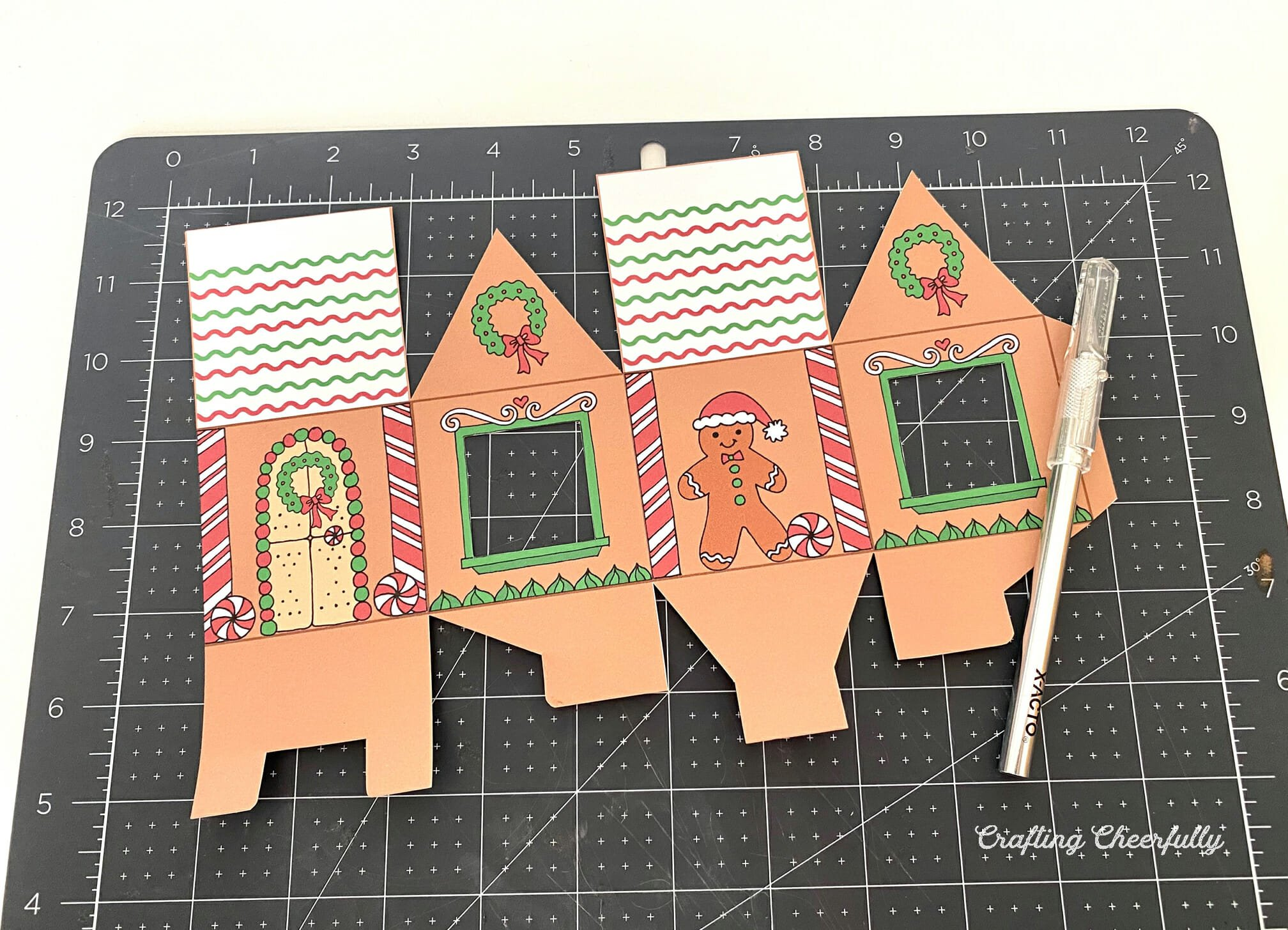 A gingerbread house treat box lays on a black cutting mat with an Xacto knife.