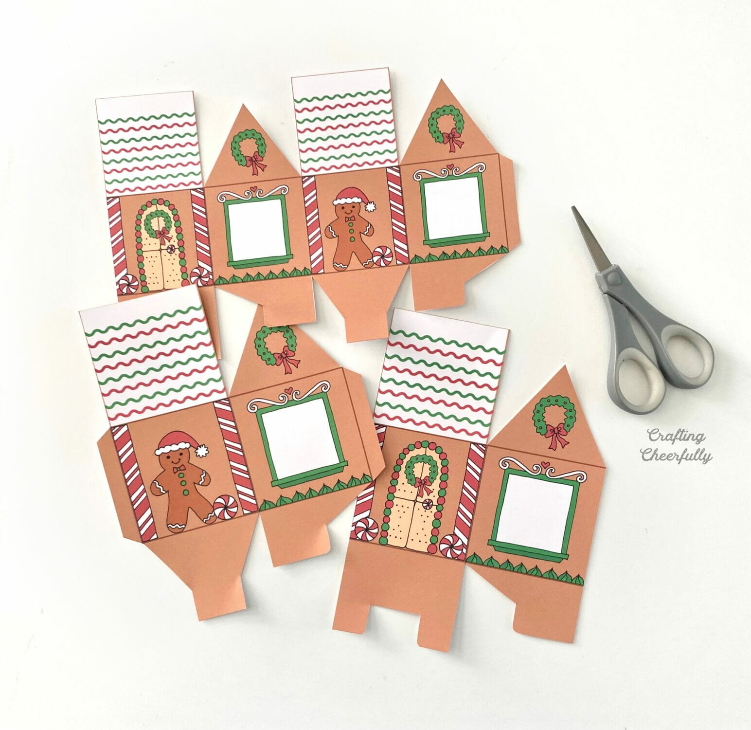 Two gingerbread house treat boxes lay next to a scissors.