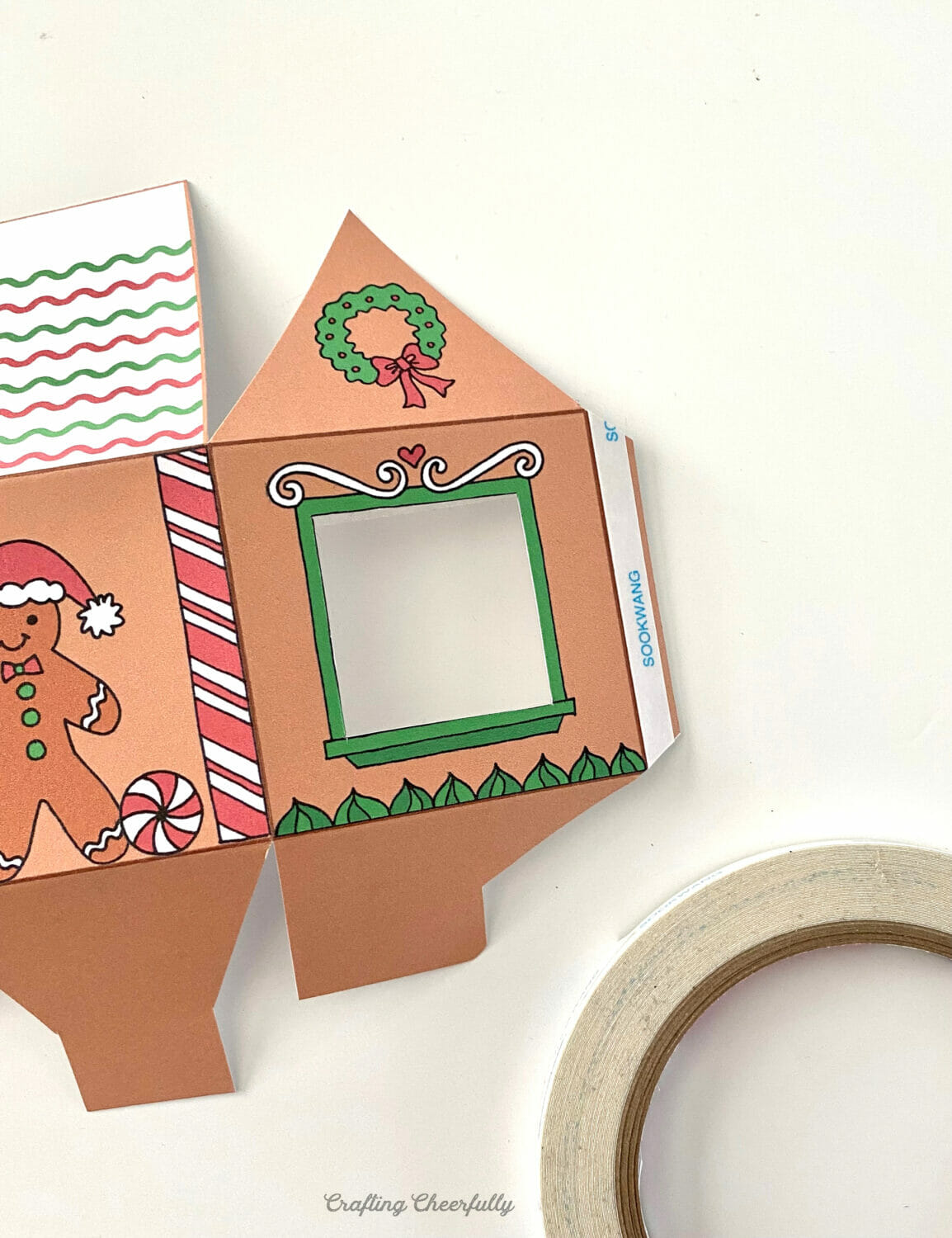 Gingerbread house treat box has double-sided tape applied to it's tab.