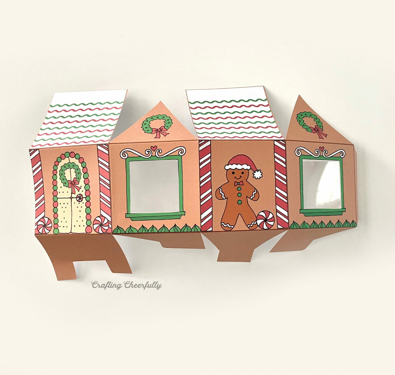 A gingerbread house treat box is folded and laying on a white table.