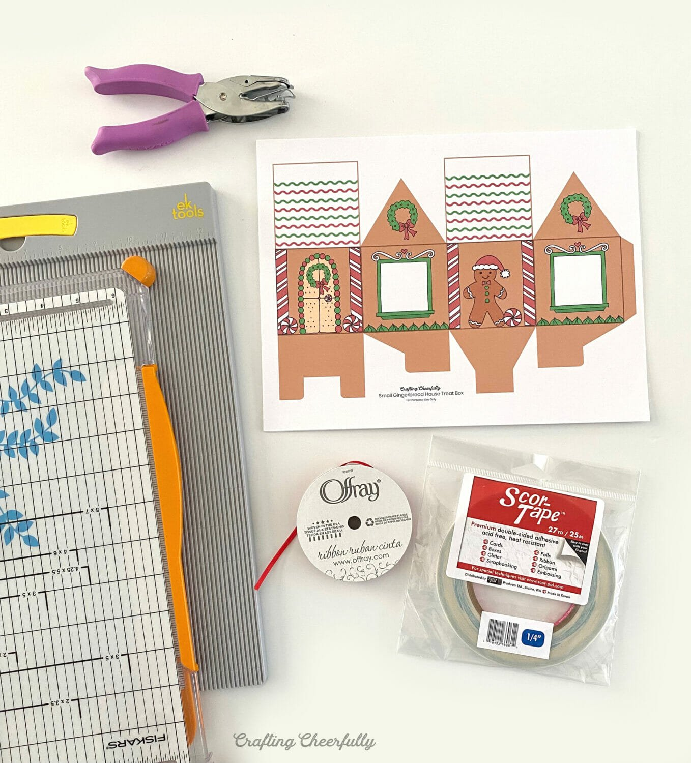 Supplies needed for the gingerbread house treat boxes like a hole punch, paper trimmer, double-sided tape and scoring board.