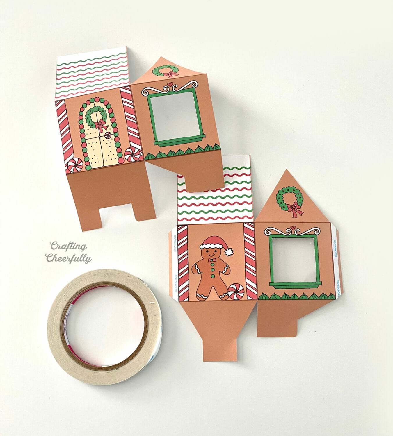 Gingerbread house treat boxes lay next to a roll of double-sided tape.