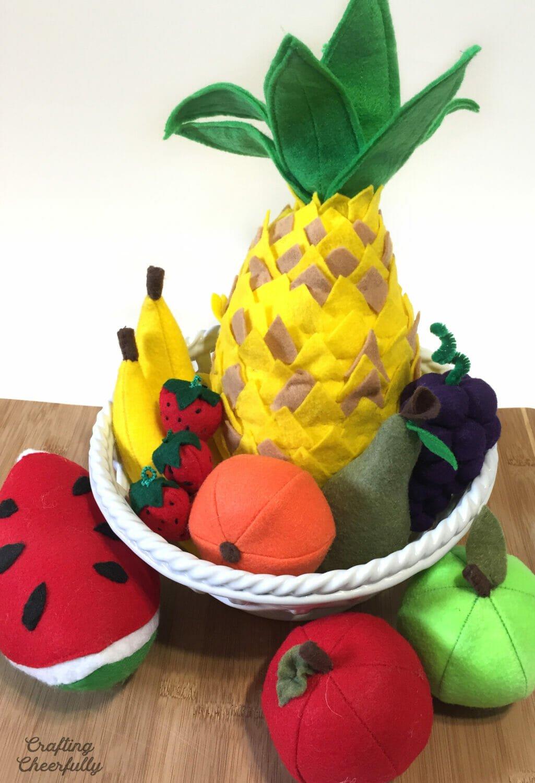 Handmade felt play fruit in a white basket on a cutting board.