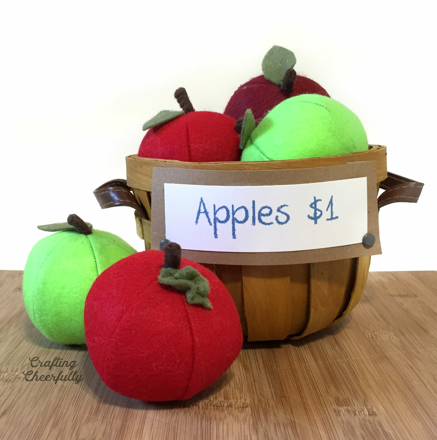 A basket of handmade felt play food apples with a sign that reads Apples $1.