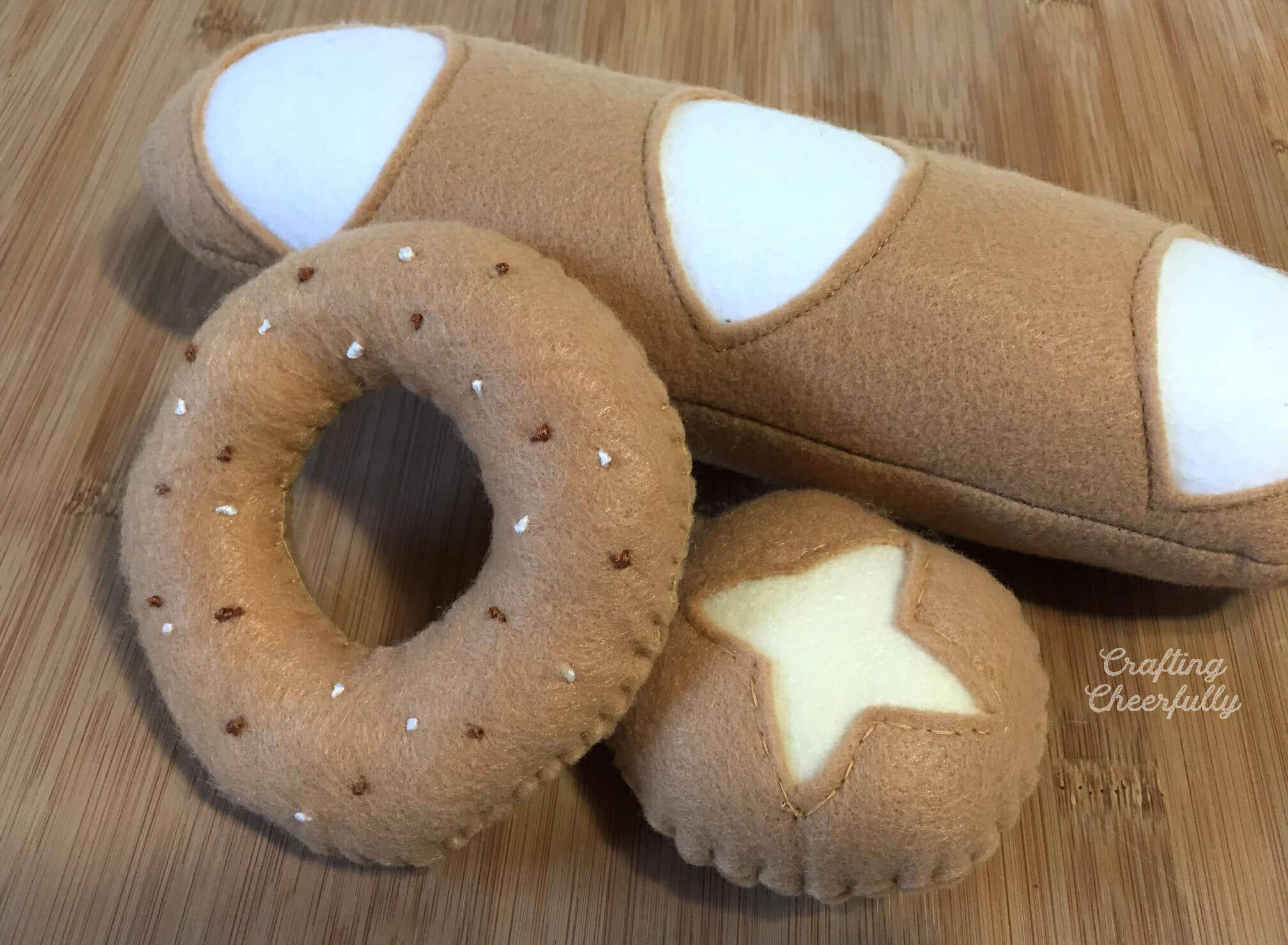 Handmade felt bread lays on a cutting board.