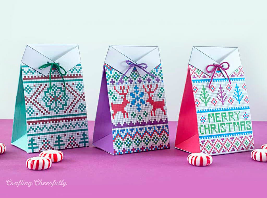 Colorful paper treat boxes designed to look like holiday sweaters sit on a pink surface.