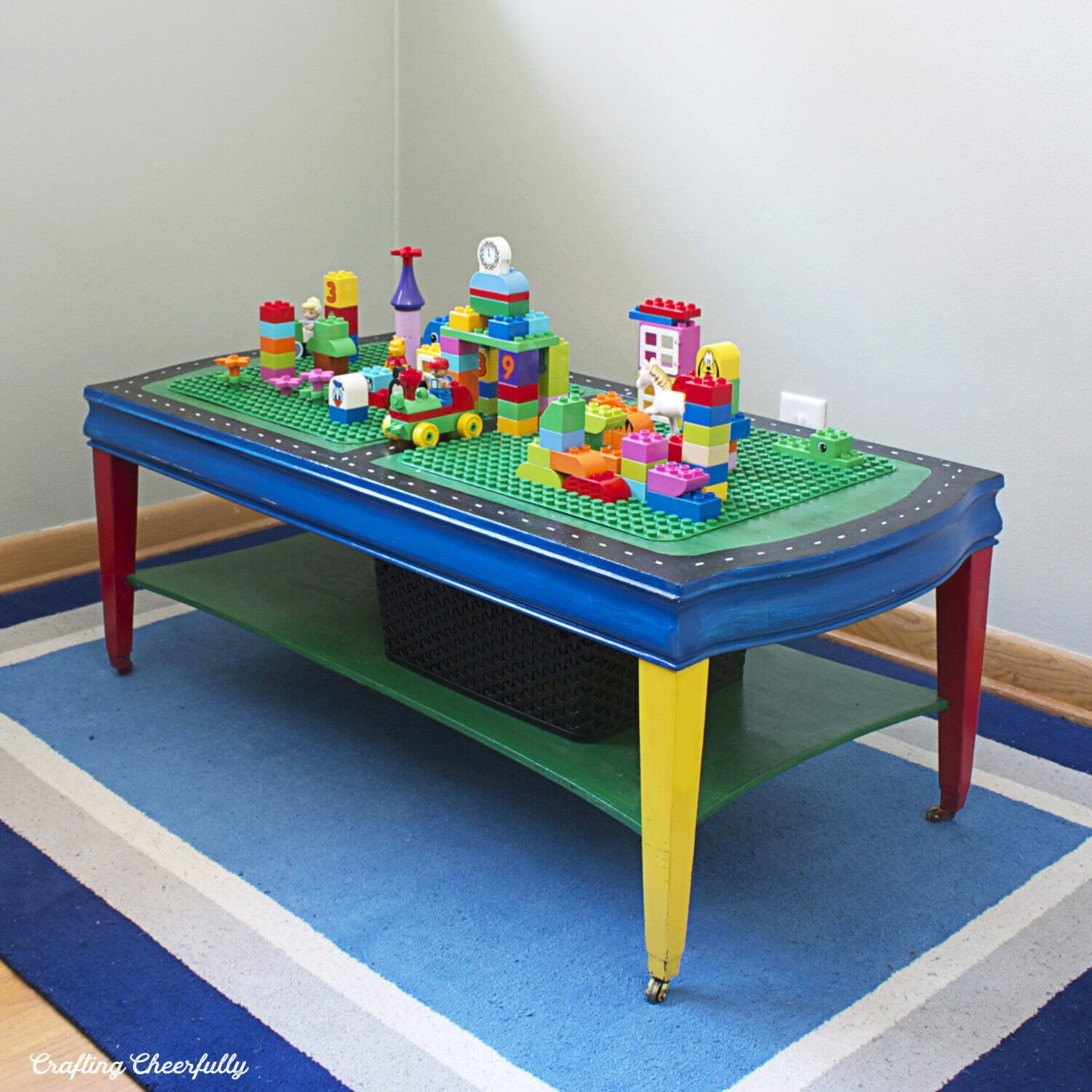 A homemade lego table made with a coffee table sits on a colorful rug.