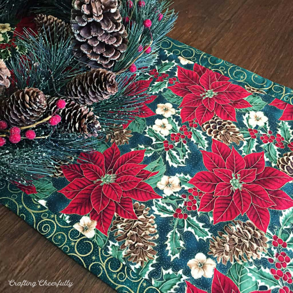 Holiday table runner made from red and green holiday fabric lays across a wooden table.