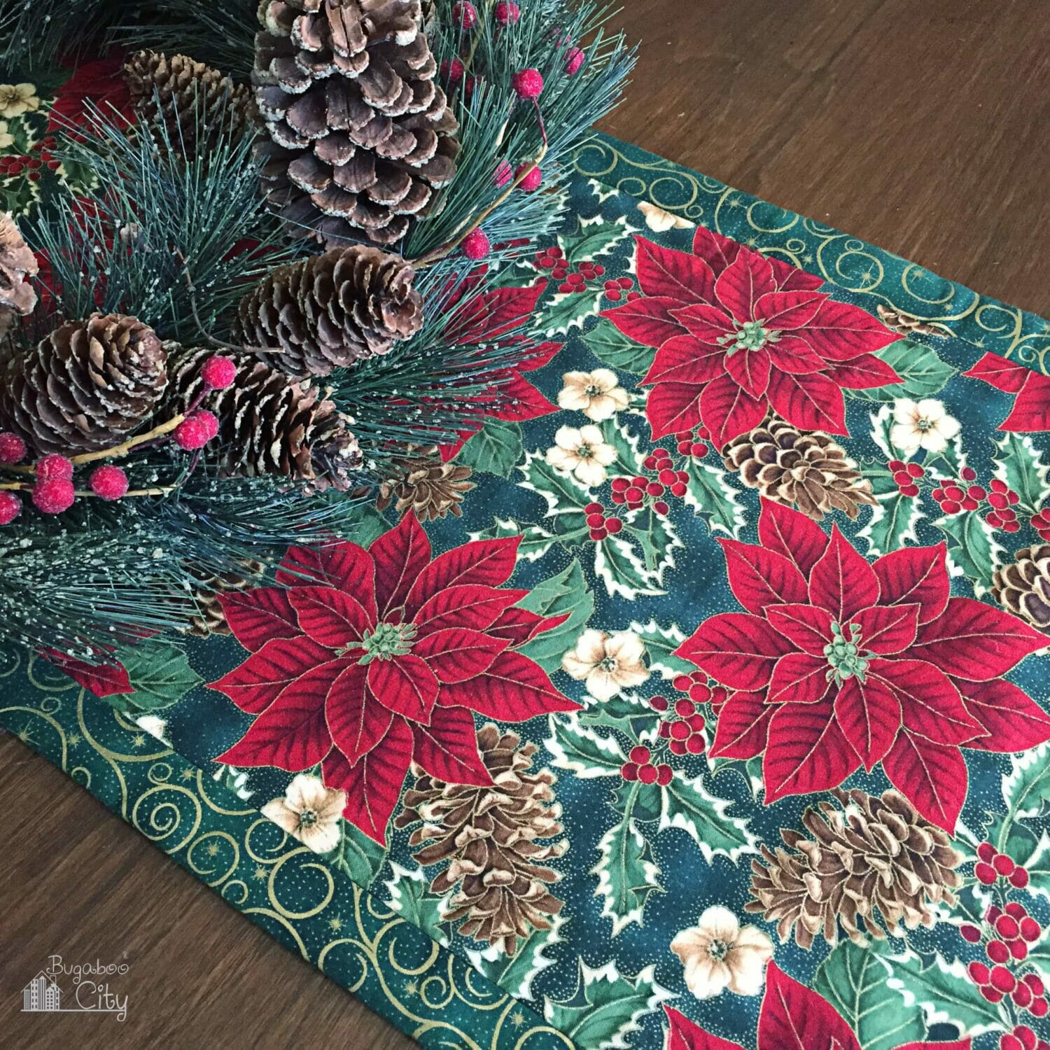Red and green printed fabric table runner on a wooden table.