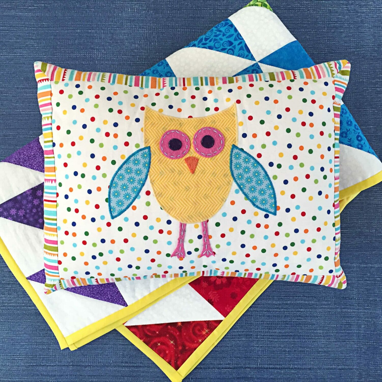 Polka dot owl pillow laying on top of a rainbow quilt and blue background.