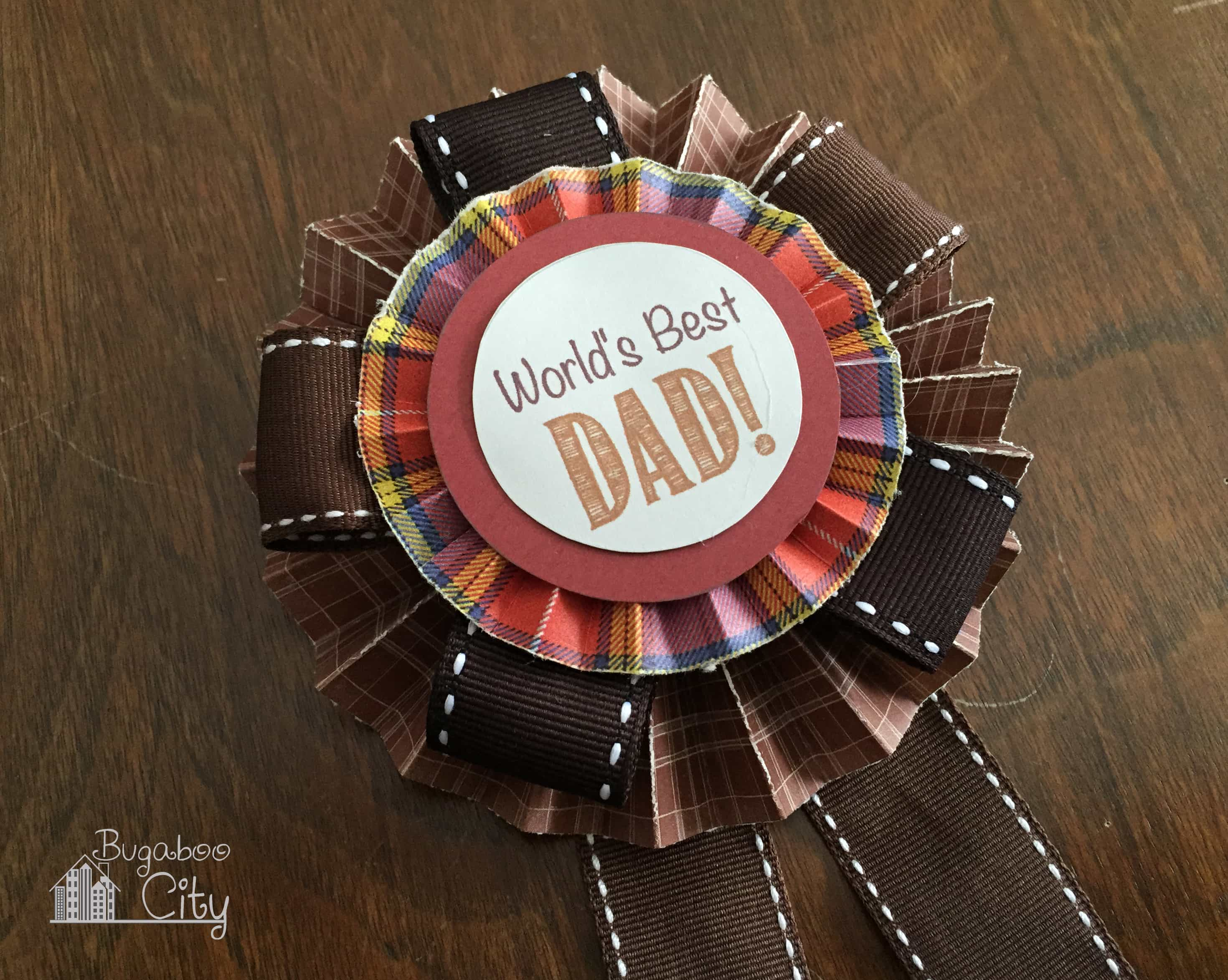 """Paper medallion that reads """"World's Best Dad"""" on a wooden table."""