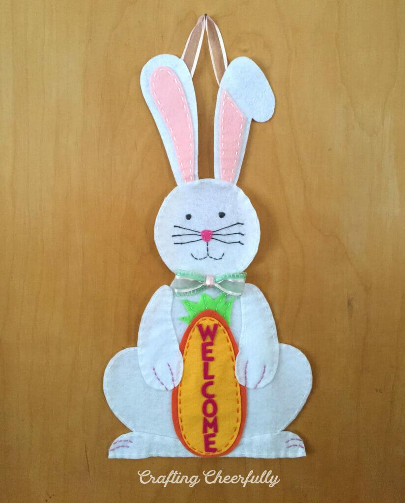 White felt bunny holding an orange felt carrot hanging on a wooden door.