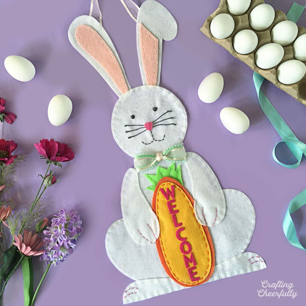 White felt bunny holding an orange felt carrot lays on a purple table with eggs, flowers and ribbon around it.