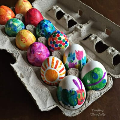 An egg carton filled with eggs decorated like The Very Hungry Caterpillar.