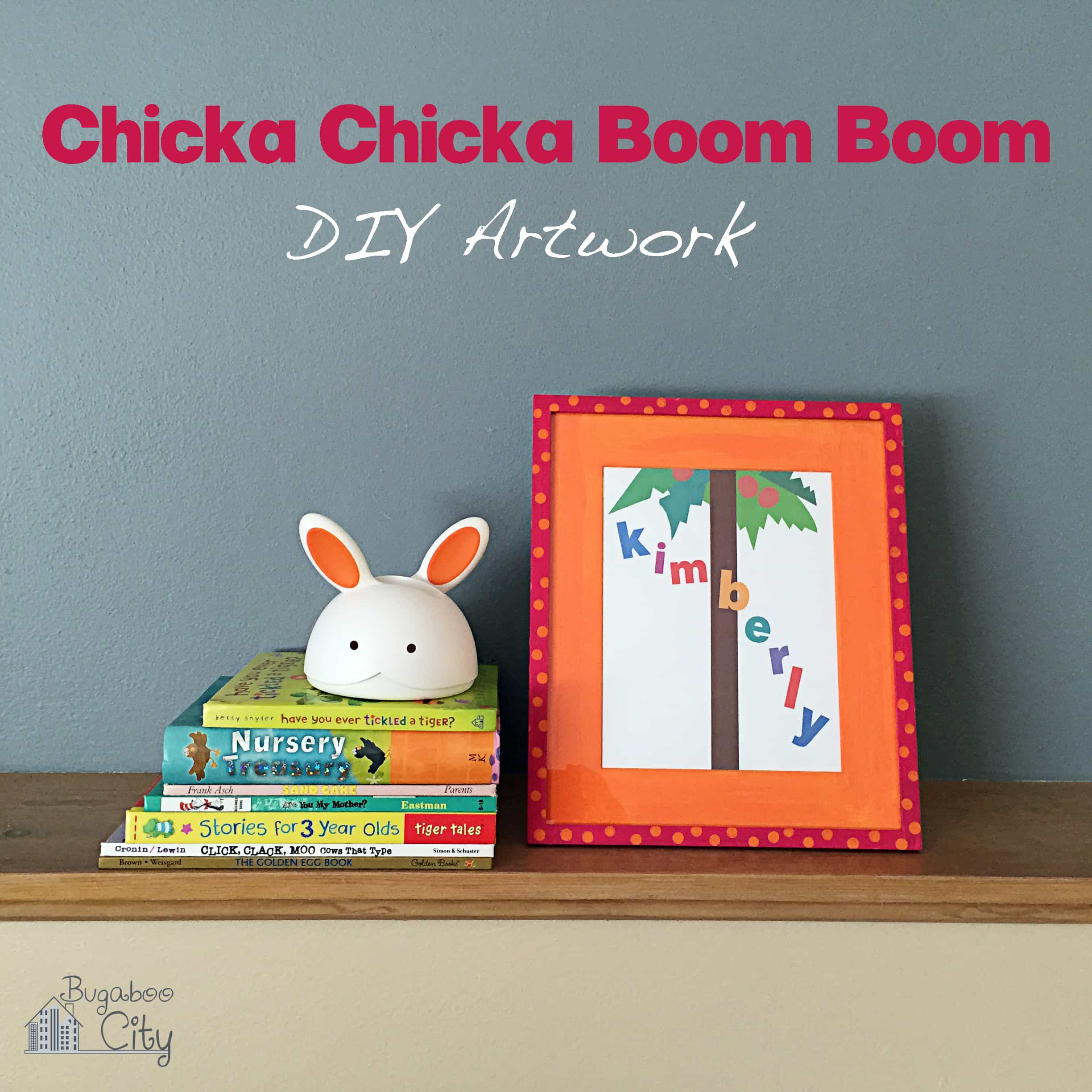 Chicca Chicca Boom Boom artwork in an orange and pink frame sits on a shelf with baby books and a bunny rabbit.