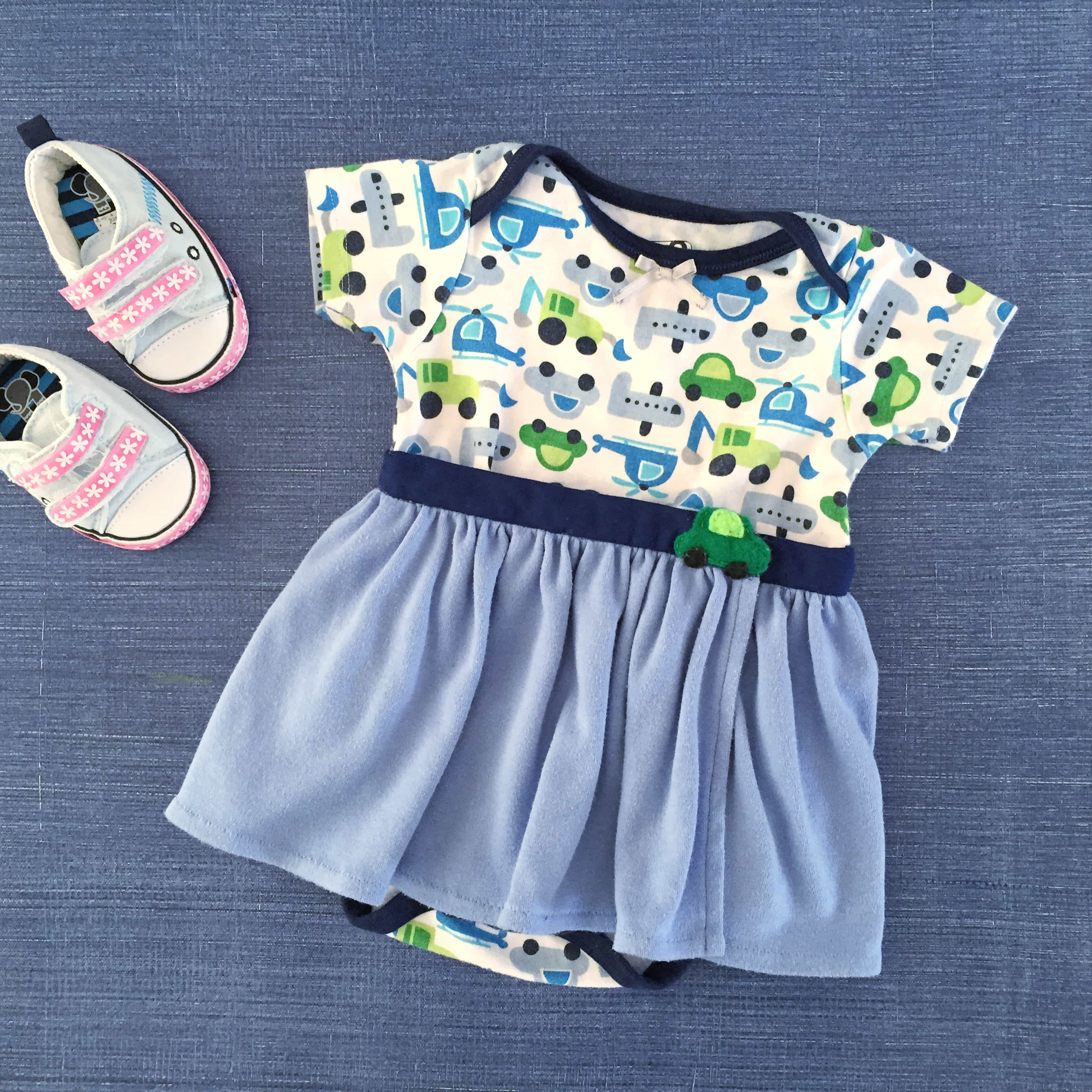 Baby onesie with cars and trucks on it with an attached blue skirt.