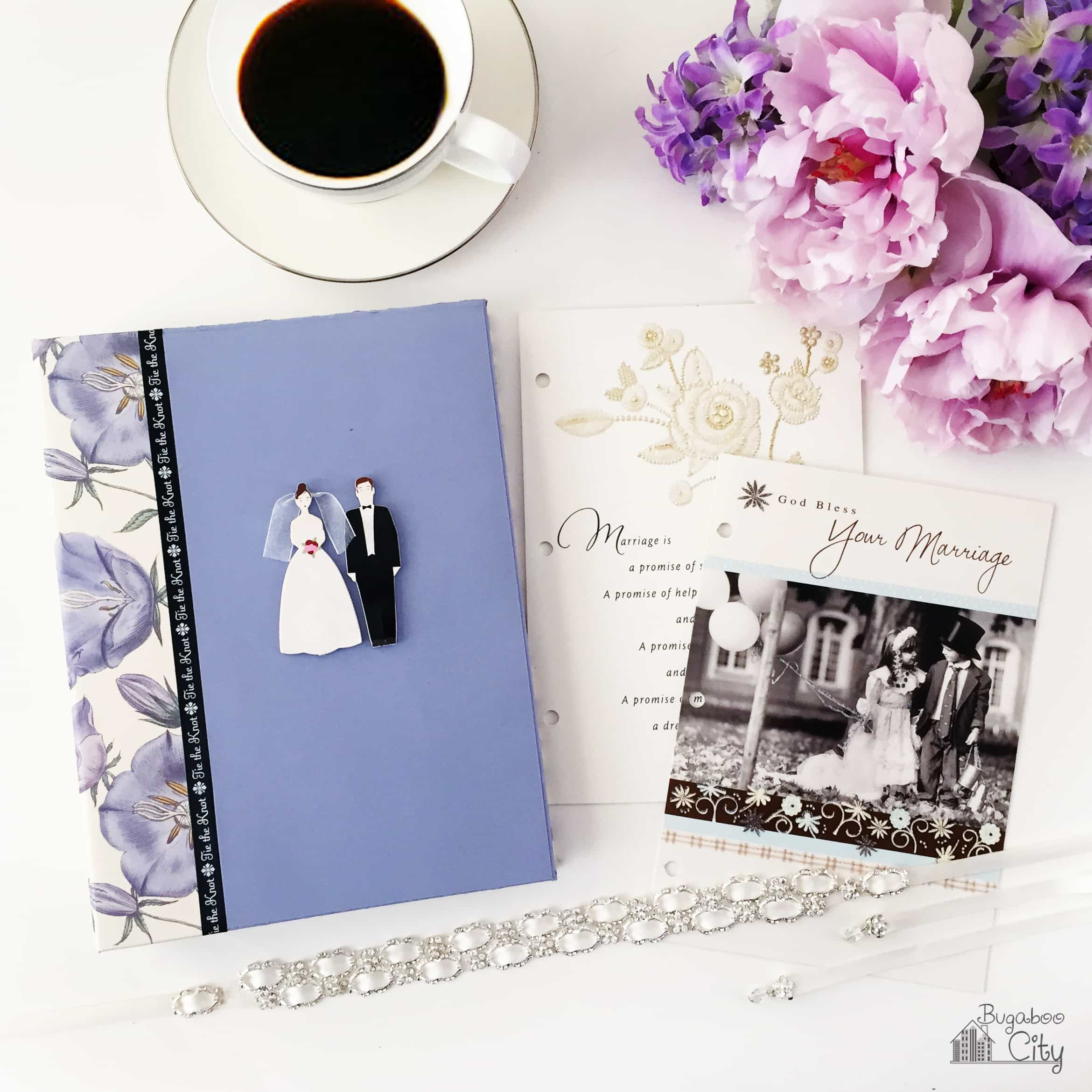 Wedding Card scrapbook sits next to fresh flowers, a cup of coffee and wedding cards.
