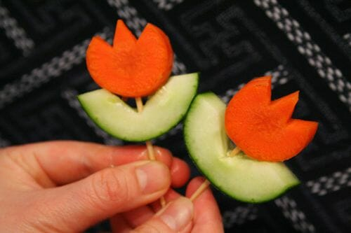 Carrots and cucumbers are used to create a cute flower with a toothpick.