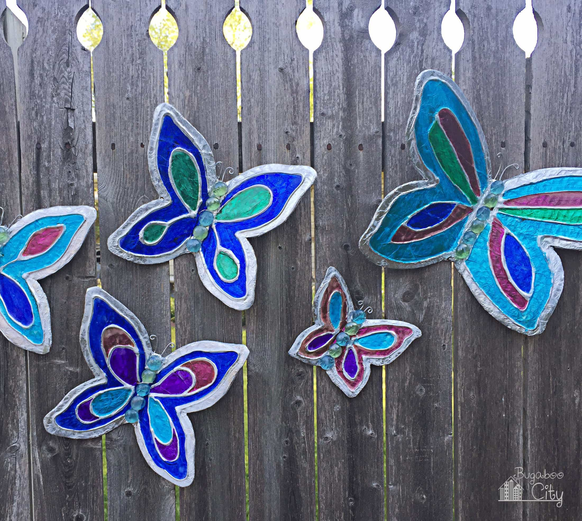 Colorful butterflies made from cardboard and tin foil on a wooden fence.