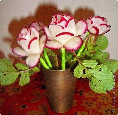 Radishes cuts into the shape of flowers and put in a vase.