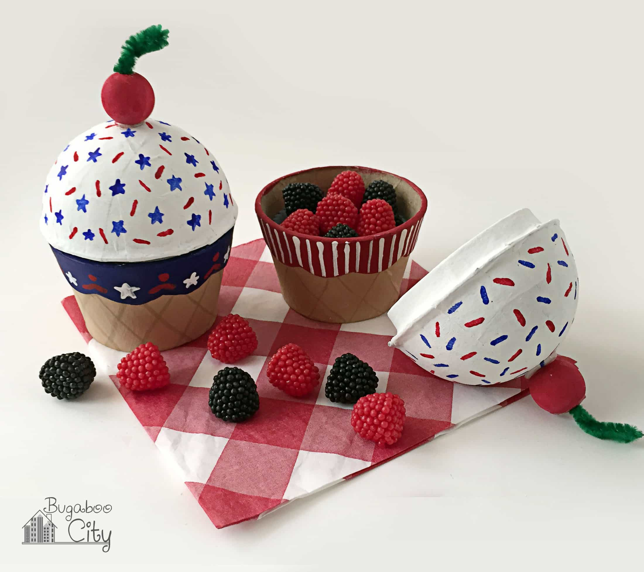 Cupcake shaped treat boxes decorated with red, white and blue sitting on a red gingham napkin.