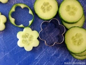 Cucumbers are cut into the shape of a flower using a flower cookie cutter.