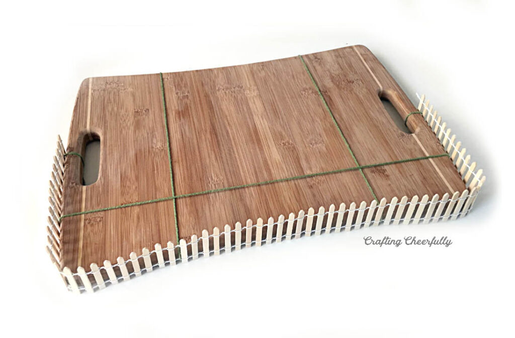 A wooden fence is attached to one side of a wooden cutting board.