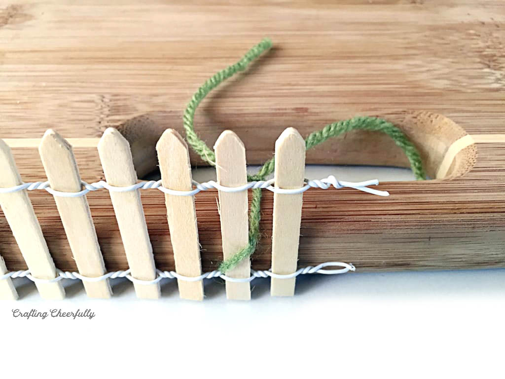 Yarn is used to tie the end of wooden fencing to the handle of a cutting board.