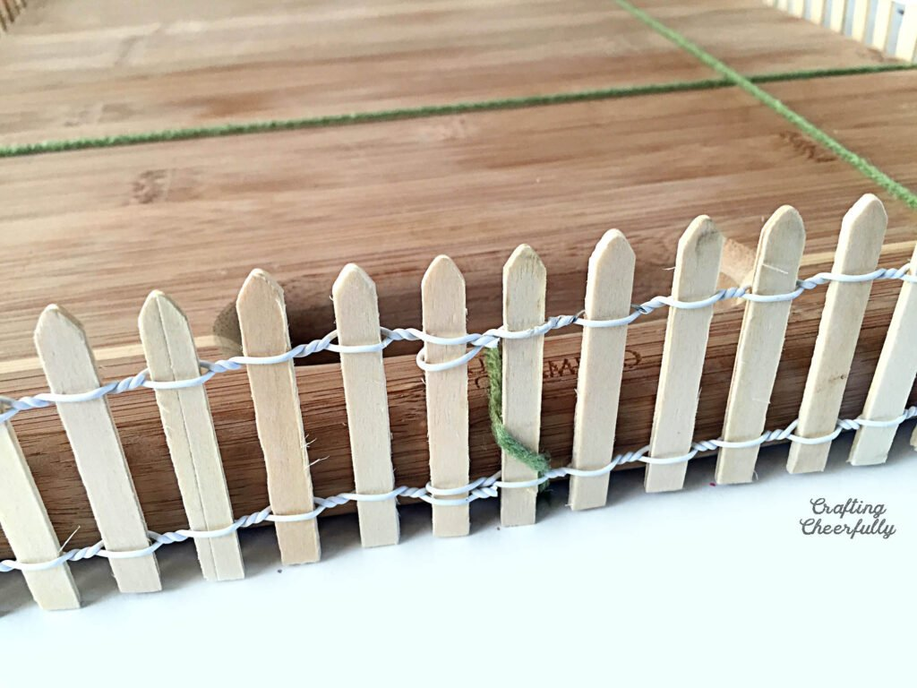A close up picture of fencing attached to the handle of a cutting board.