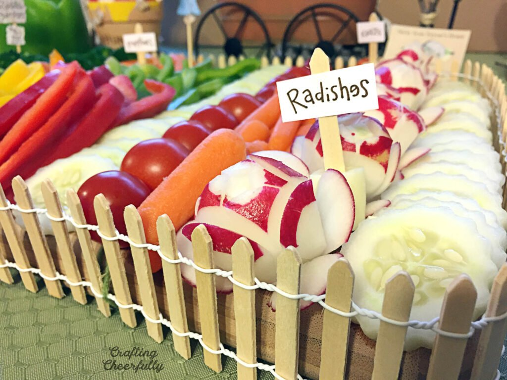"A close up picture of radishes on the cutting board with a little garden sign that says ""Radishes""."