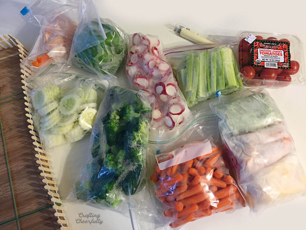 Bags of vegetables lay next to a cutting board.