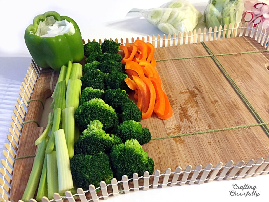 Celery, broccoli and peppers are one side of the cutting board.