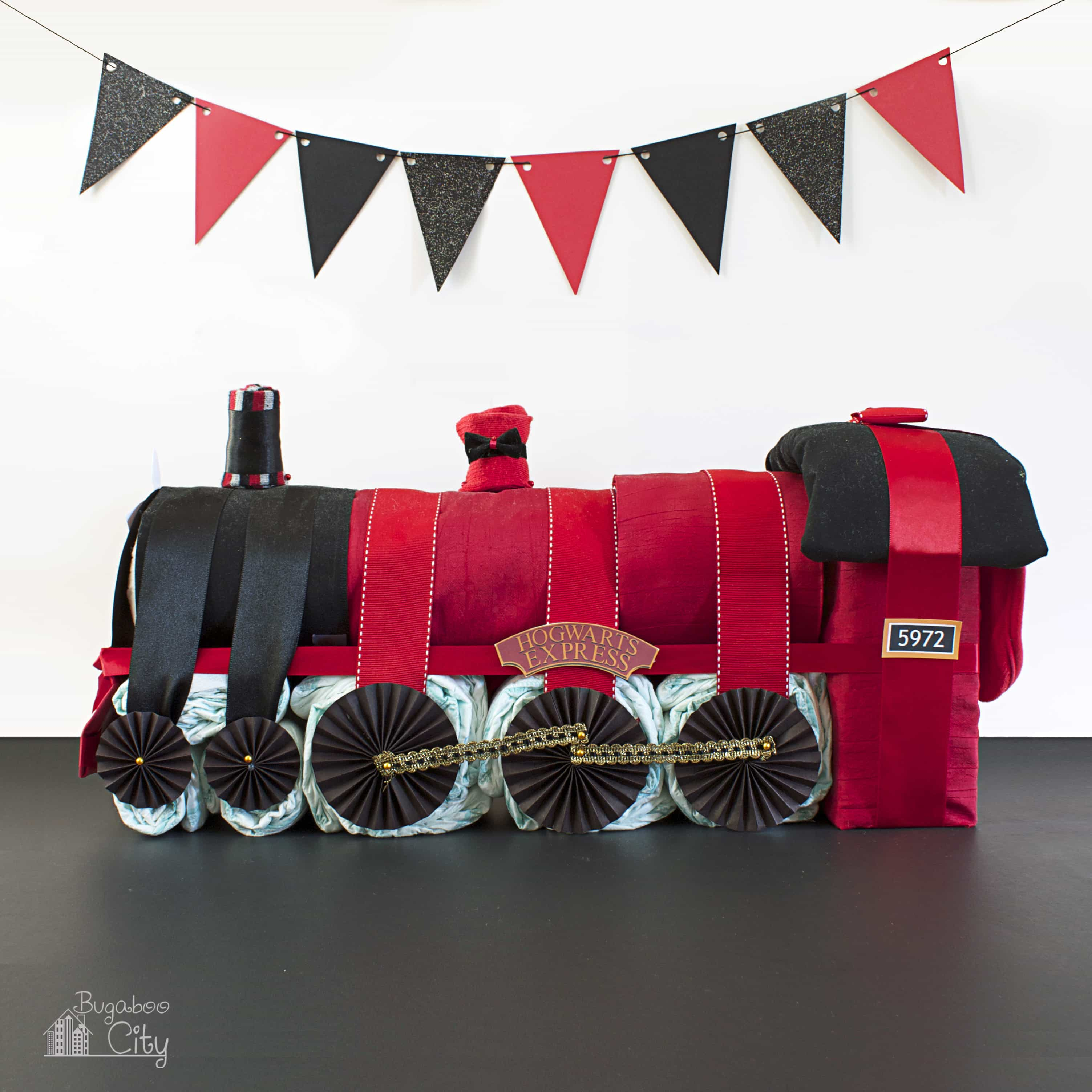 Hogwarts Express Diaper Cake witha red and black paper banner hanging behind it.