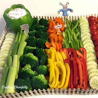 Vegetable platter with a cute fence around it and a scarecrow.
