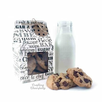 Milk carton style treat box with cookie gift tag sits next to chocolate chip cookies and a bottle of milk.